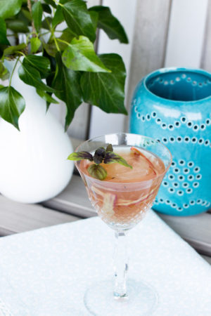 Martini-cocktail mit Rhabarbersirup und Basilikum